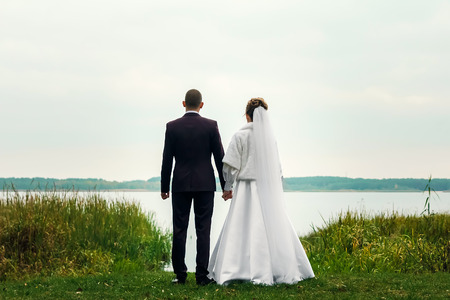 bride and groom standing in front of the lake and looking into the distance in the direction of the park Valentines Day
