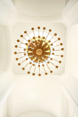 Gilded chandelier against the white ceiling bottom view Фото со стока