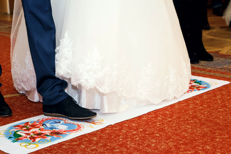 Newlyweds stand on the red wedding towel Stock Photo