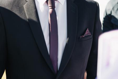 Ein Mann im blauen Anzug glättet seine Ärmel