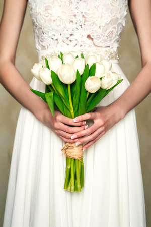 The bride holds a beautiful bouquet of flowers on a background of lake Imagens