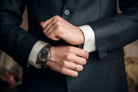 A man buttoning a black jacket watch on hand