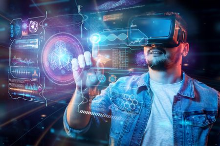 Portrait of a man with glasses of virtual reality, vr, interacts with a virtual screen. The concept of the future is here, applications complement reality, the interface of virtual reality Stock Photo
