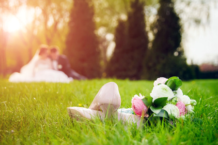 Beautiful wedding bouquet and shoes on a green grass