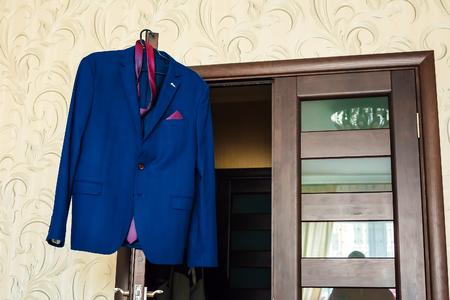 Jacket, tie and shirt hanging blue jacket, brown door, yellow walls