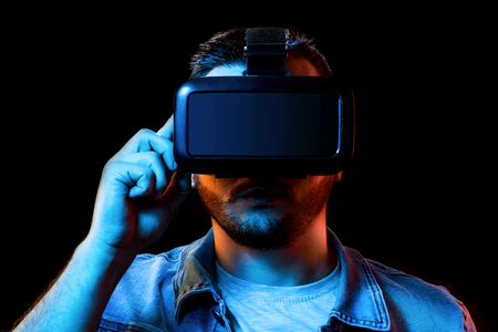 Portrait of a man in virtual reality glasses, vr, against a dark background. The concept of the future is here, applications complement reality, the virtual reality interface. Copy space.