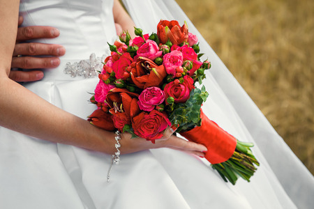 The bride is holding a wedding bouquet in her hands in nature