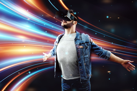 Portrait of a man wearing virtual reality glasses, vr, against a dark background, playing a game. The concept of the future is here, applications complement reality, the virtual reality interface.
