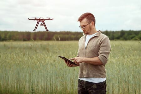 A male farmer manages a drone over agricultural land. Technology, innovation to increase productivity, modern agriculture.