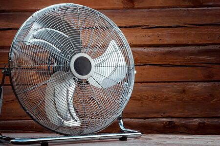 Large tabletop ventilator on the table against the background of a wooden wall. The concept of heat, hot weather, air conditioning.