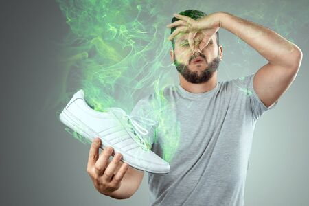 A man holds sneakers in his hands. Nasty smell. Stink legs, fungus on the legs.