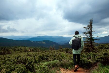 Creative background, A male tourist walks through a mountainous area with a backpack. The concept of active tourism, recreation, the Carpathians. Copy space. Banco de Imagens