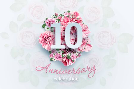 Creative background lettering 10 numbers and anniversary celebration text on pink flowers background. Anniversary concept, birthday, celebration event, template, flyer.
