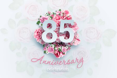 Creative background lettering 85 numbers and anniversary celebration text on pink flowers background. Anniversary concept, birthday, celebration event, template, flyer.