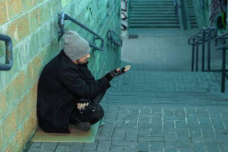A man, homeless, a man asks for alms on the street. Concept of homeless person, addict, poverty, despair Zdjęcie Seryjne