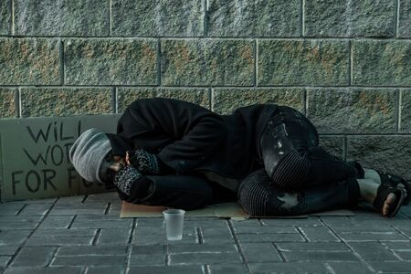 A man, homeless, a man sleeping on a cold floor in the street with a Help sign. Concept of a homeless person, social problem, addict, poverty, despair