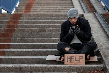 A man, homeless, a person asks for alms on the street with a Help sign. Concept of homeless person, addict, poverty, despair
