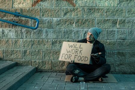 A man, homeless, a man asks for alms on the street with a sign will work for food. Concept of homeless person, addict, poverty, despair