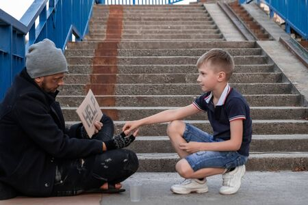 The boy helps the homeless on the street. Concept of a homeless person, social problem, addict, poverty, despair Stock Photo