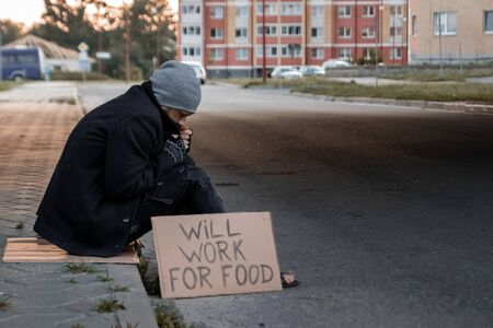 A man, homeless, a man asks for alms on the street with a sign will work for food. Concept of a homeless person, social problem, addict, poverty, despair Standard-Bild