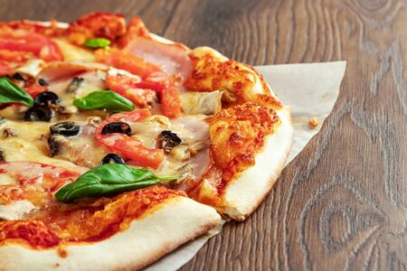 Pizza on a wooden background with ham, olives, tomatoes and green basil. Itolyan cuisine, copy space
