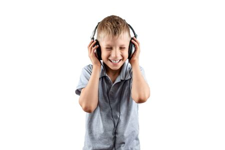 White smiling boy listens to music in big headphones Isolated on a white background. Musician, the future of the child, music lover