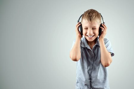 White smiling boy listens to music in large headphones on a light background. Musician, the future of the child, music lover