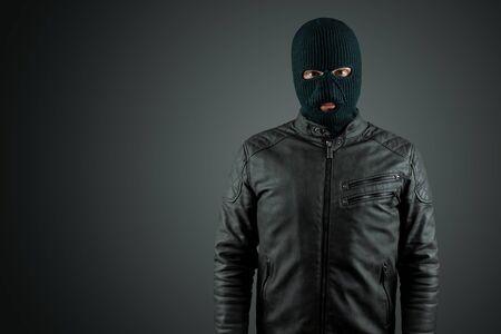Robber, thug in a balaclava on a black background. Robbery, hacker, crime, theft. Copy space Zdjęcie Seryjne