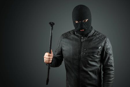 Robber, bandit in a balaclava with a crowbar in his hands on a black background. Robbery, hacker, crime, theft. Copy space