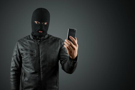 Robber, thug in a balaclava with a phone in his hands on a black background. Robbery, hacker, crime, theft. Copy space.