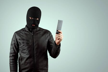Robber, bandit in a balaclava with a phone in his hands on a light background. Robbery, hacker, crime, theft. Copy space