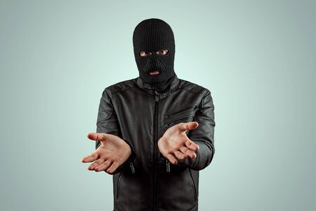 Robber, bandit in a balaclava surrenders on a light background. Robbery, hacker, crime, theft. Copy space