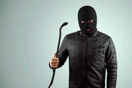 Robber, bandit in a balaclava with a crowbar in his hands on a light background. Robbery, hacker, crime, theft. Copy space