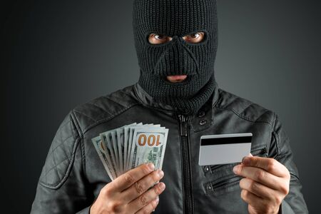 Robber, a thug in a balaclava holds a credit card in his hands on a dark background. Robbery, hacker, crime, theft. Copy space