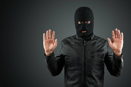 Robber, a thug in a balaclava raised his hands on a black background, surrenders. Robbery, hacker, crime, theft, arrest. Copy space Zdjęcie Seryjne