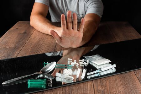 A man with a stop gesture refuses drugs, the fight against drug addiction. Social problem, drug addiction, death, addiction. Copy space Archivio Fotografico