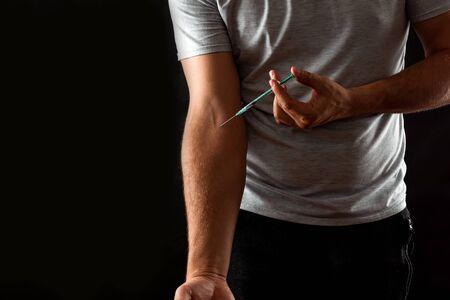 A man injects a syringe into a vein on a black background. Social problem, drug addiction, death, addiction. Copy space Banco de Imagens