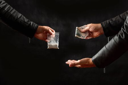 Hand of a drug addict with money, buying a dose of cocaine or another drug from a drug dealer on a black background. Social issue, drug addiction. Copy space Stock Photo