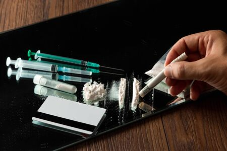 Hand with a tube of dollars, tracks of cocaine, a bunch of different drugs, syringes, pills on the table. Social problem, drug addiction, death, addiction. Copy space