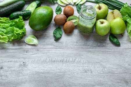 Fresh green food on a light table. Avocados cucumbers cabbage apples beans kiwi onions broccoli. The concept of healthy food, detox vegetarianism. Copy space flat lay