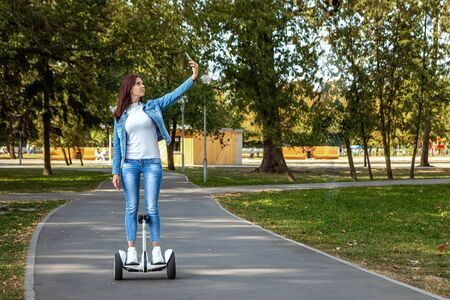 Beautiful girl on a white hoverboard in the park, self-balancing scooter. Active lifestyle technology future copy space.