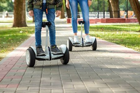 A young couple riding a hoverboard in a park, self-balancing scooter. Active lifestyle technology future.