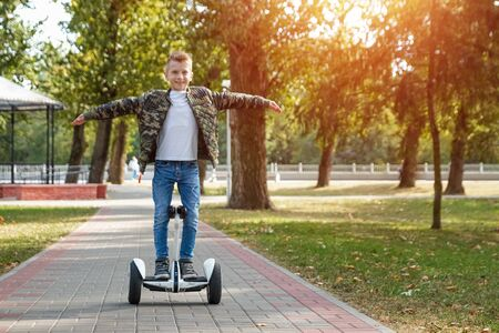 A boy riding a hoverboard in the park, a self-balancing scooter. Active lifestyle technology future. Reklamní fotografie