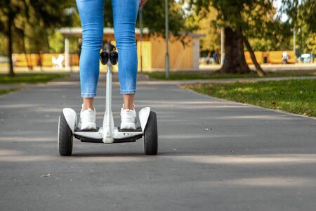 Legs of a girl in white sneakers on a white hoverboard, self-balancing scooter in a park close-up. Active lifestyle technology future copy space.