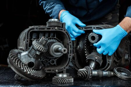 Hands of a male repairman in blue gloves on a background of a gearbox, close-up. Repair box predach, repair of used cars. Metal background.