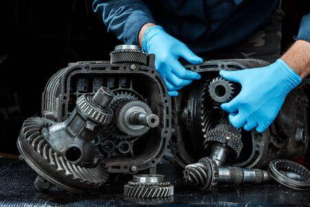 Mani di un riparatore maschio in guanti blu su uno sfondo di un cambio, primo piano. Riparazione box predach, riparazione di autoveicoli usati. Sfondo di metallo.