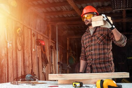 Builder man carries boards on his shoulder. Construction work, repair