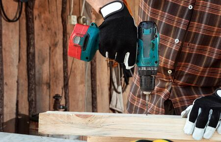 A man carpenter twists a screw into a tree with an electric screwdriver, male hands with a screwdriver close-up. Work with wood Banque d'images