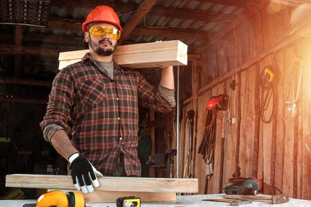 Builder man carries boards on his shoulder. Construction work, repair Stock Photo