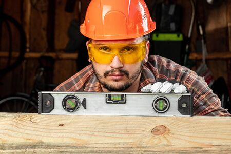 Builder man looks at the construction level checks the horizontal surface, male hands with a level close-up. Construction work, repair Stock Photo